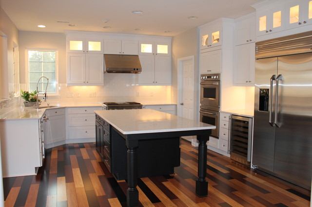 white kitchen with black island, multi-colored bamboo flooring .