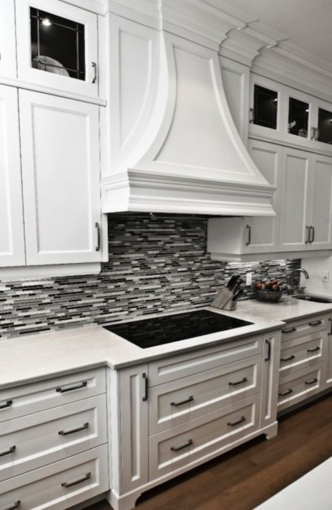 Gorgeous kitchen with crisp white cabinetry, marble countertops .