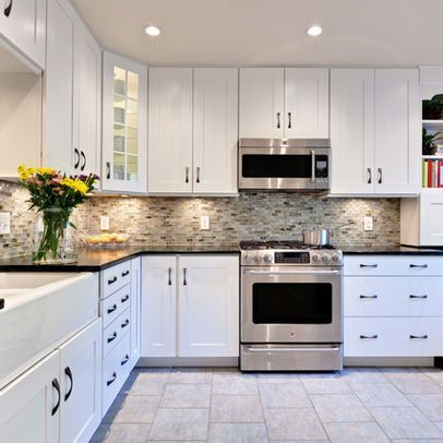 White cabinets with the multi backsplash, dark counters and gray .