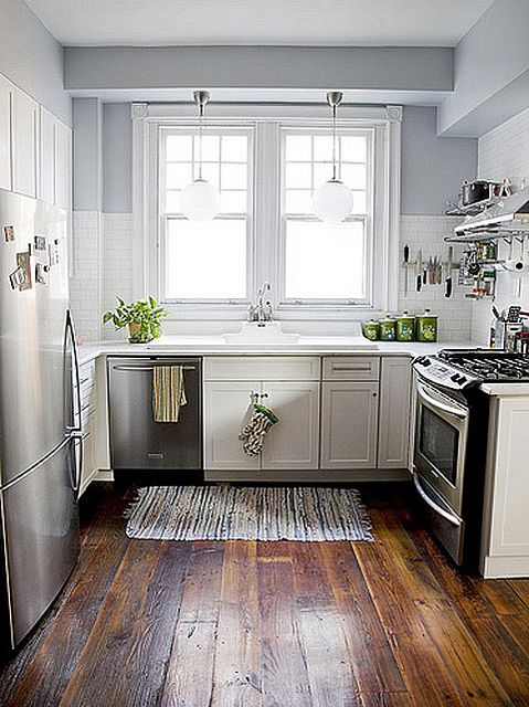 Galley Kitchen with white cabinets and dark stained, wide plank .