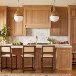 Honey Stained Oak Kitchen Cabinets with Brass Pendants .