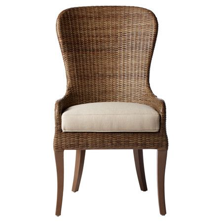 The subtle curves and high back of this rattan dining chair pair .