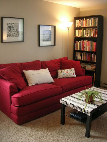 Red couch, light floors, dark furniture. This is the theme we are .
