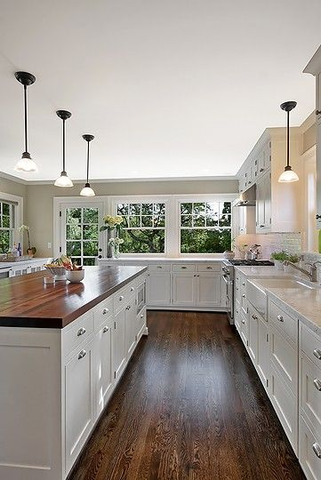 White cabinets, dark wood floor, white subway tile, marble counter .