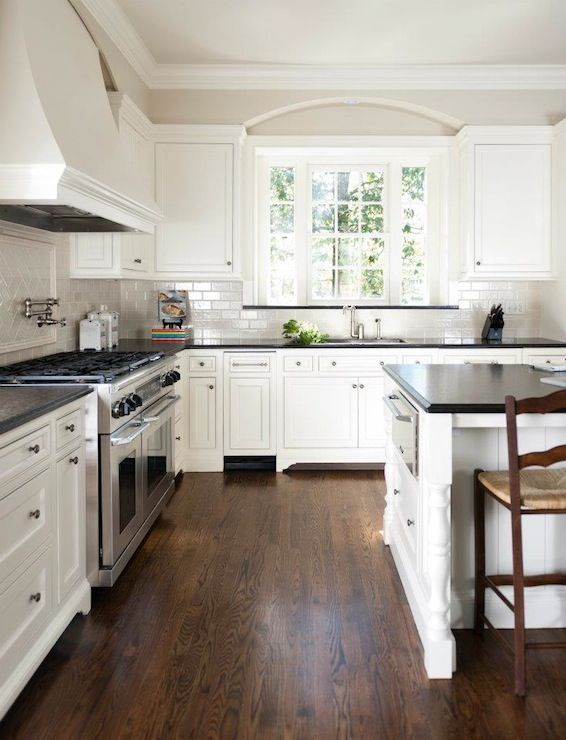 Love the dark wood, white cabinets, and grey tile   Black kitchen .